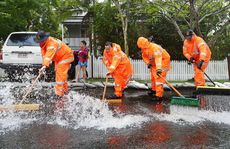 MASS CLEAN-UP: SES volunteers work together to sweep pooling water from a flooding home on Joyce St, East Ipswich.