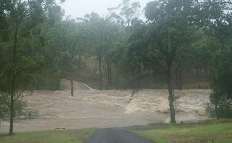 Floodwaters rage over Dingo Mountain Road near Crows Nest.