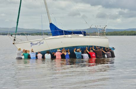 Tin Can Bay locals band together to refloat a stricken yacht at the bay.