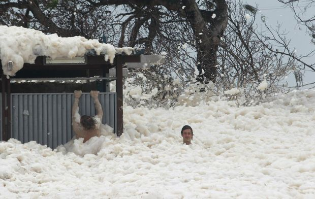 Foam whipped up by heavy rain and huge seas coats the coastline on the Sunshine Coast, attracting a lot ot attention from spectators. A couple of young males reach a public toilet block after trudging through head-high foam at Alexandra Headland.