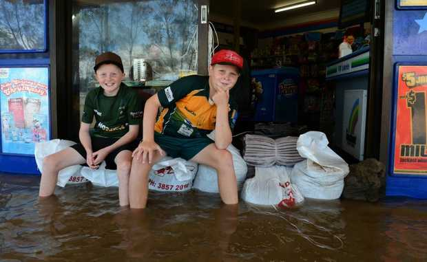 Taylor and Parker Bryant on some sand bags in front of Chinderah News.