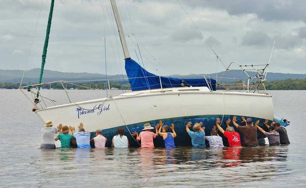 Tin Can Bay locals band together to refloat a stricken yacht which, earlier yesterday, was left high and dry in the bay.