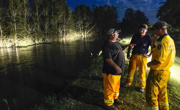 WATCHING BRIEF: Rural Fire Service volunteers check the top of the levee for heights and any weakness as the Clarence River rises in darkness at Maclean.