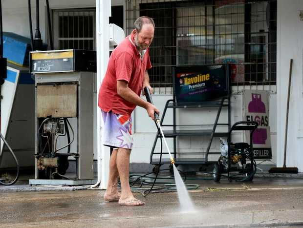 Taylor's Corner co-owner Steve Brown cleans mud from outside his shop at Murwillumbah.