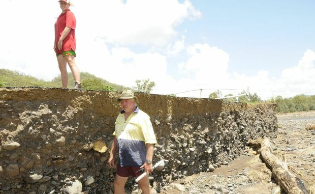 Junction View residents Chloe Kennedy (left) and Peter Coleman standing beside what is left of a 20 kilometre section of Mount Sylvia Road.