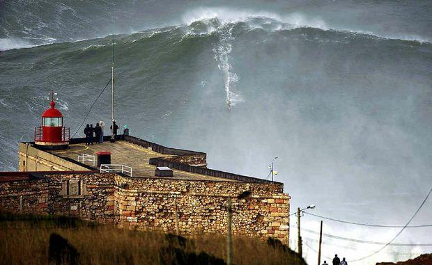 Surfer Garrett McNamara, 45, rides this wave, said to be a world-record 30m, off Praia do Norte beach in Nazare, Portugal.