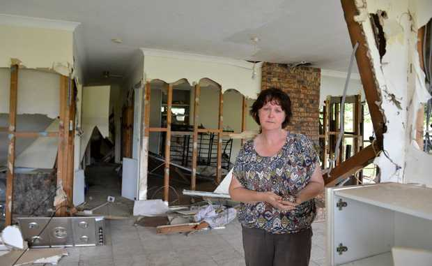 Maureen Sharkey stands in what is left of her Lower Wonga home, washed away by freak flooding in Widgee Creek on Sunday morning.