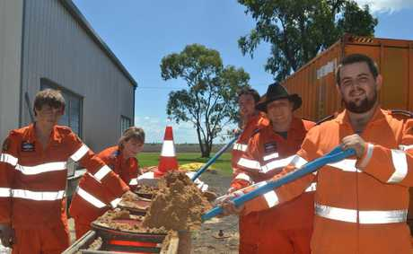 Bo Richards, Jane Holdsworth, Reece Graham, Justin Clark and Damien Pointon fill sandbags to block floodwater.