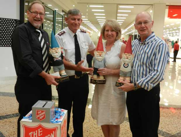 Chris Worboys (left) hands the cheque to Major Steve Metcher after Sharon and John Shaw bid farewell to their gnomes.