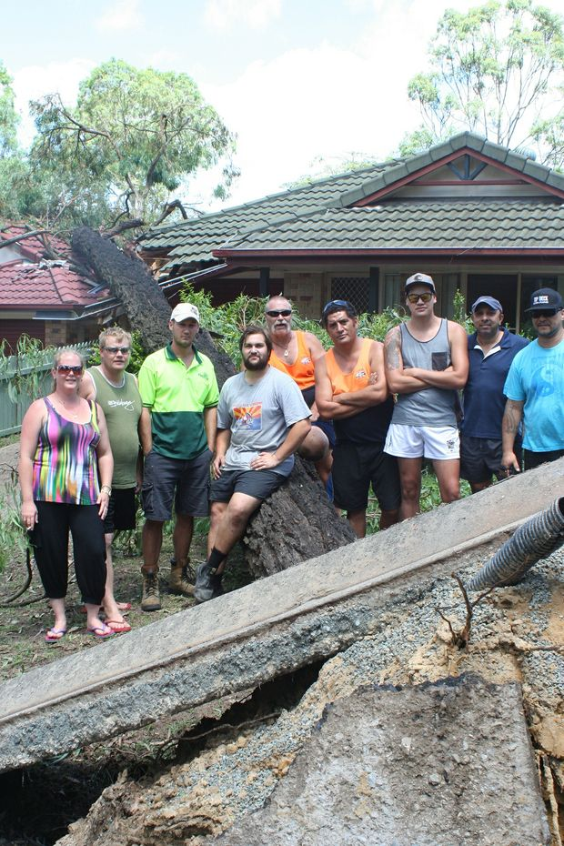 Residents from Fraser Plc in Forest Lake gather around a tree which fell and crushed a home in their street during this month's fierce storm.