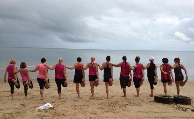The Wide Bay Crew do some stretching at a Hervey Bay beach before their workout.