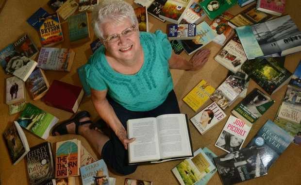Christine Smith with heaps of books for sale to raise funds for cancer.