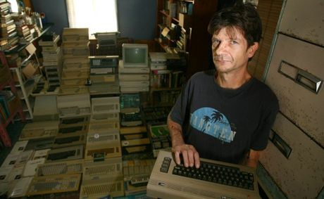 Michael Eckardt holds an old Commodore 64 dating back to the early 1980s with his collection of old computers in the back