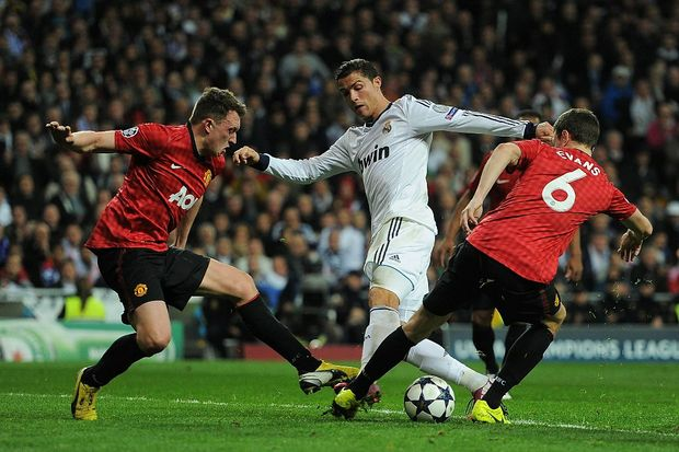 Cristiano Ronaldo of Real Madrid is put under pressure by Jonny Evans and Phil Jones of Manchester United during the UEFA Champions League Round of 16 first leg match between Real Madrid and Manchester United at Estadio Santiago Bernabeu on February 13, 2013 in Madrid, Spain.