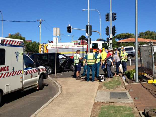 Emergency services at the scene of a collision between a black 4WD and bus at the intersection of Herries and Cohoe Sts this morning.