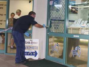 Police dust for fingerprints after a man held up a store.