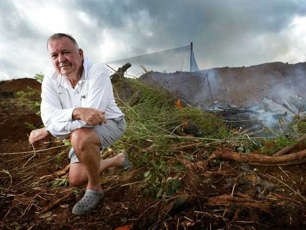 Bangalow Farmer Ray Hicks kneels next to a pit of his burning fruit trees. He will destroy 5000 trees, saying he can no longer farm fruit economically due to the Federal Goverment's ban on a chemical used to control fruit fly.