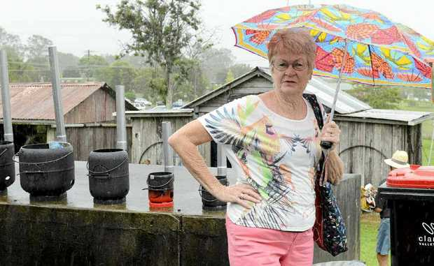 Wendy Smythe was taking cover from the rain at the official opening of the Lawrence Museum's blacksmith's hut on Saturday. Photo: Debrah Novak