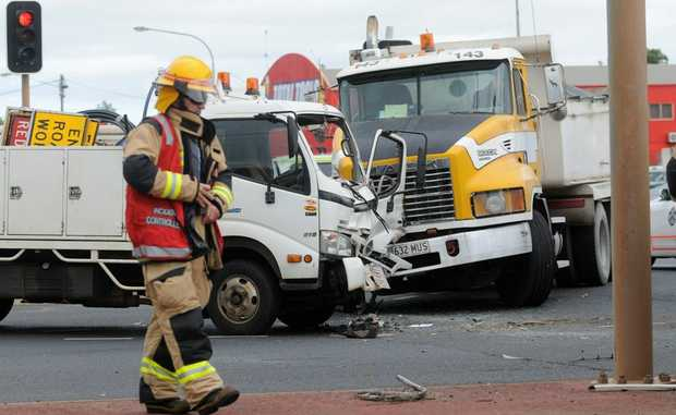 Emergency crews attend the scene of a two-truck crash at the intersection of Taylor and McDougall Sts, Toowoomba.