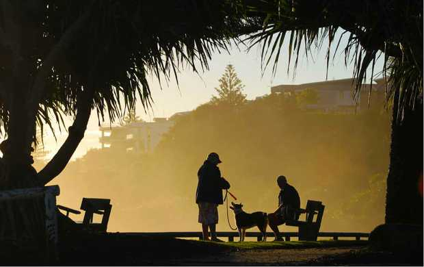 AUSSIE DAY: A couple of blokes enjoy a chat as the sun breaks through at Moffat Beach earlier this week.