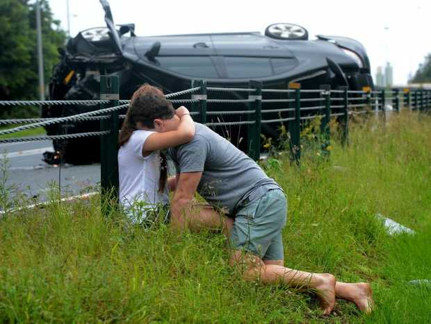 A young couple comfort each other after their car crashed on the M1 motorway.