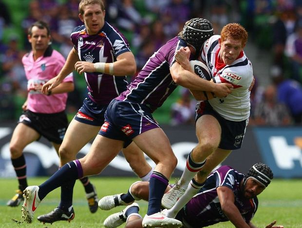 Tom Symonds of the Roosters is challenged by his opponents during the round four NRL match between the Melbourne Storm and the Sydney Roosters at AAMI Park on March 25, 2012 in Melbourne, Australia.