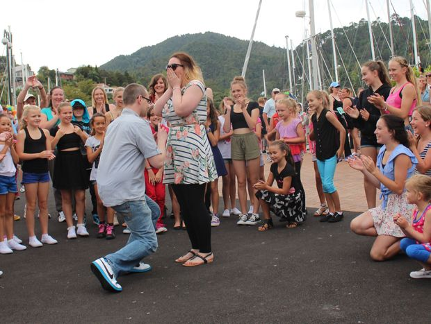 Englishman Andrew Bewley gets down on one knee to propose to partner Jenny Sanders at Whangarei Town Basin, surrounded by a dancing flash mob.