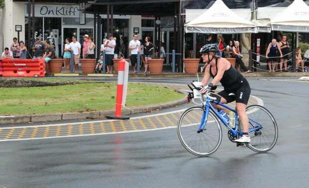 Spectators watch as Kingscliff Triathlon competitors ride past.