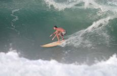 Surfers tackle waves at Point Cartwright.