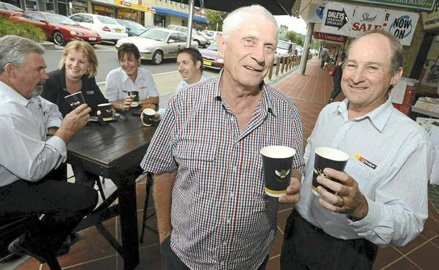 ESPRESSO: John Rees from Blueys Cafe, front left, and Paul Deegan from LJ Hooker Lismore, right, join staff from LJ Hooker in promoting the suspended coffee phenomenon.