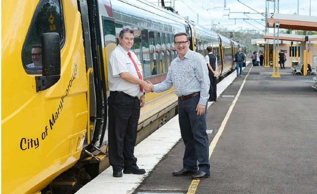Train driver Mark Driscoll is congratulated by member for Gympie David Gibson at the Gympie North Station yesterday morning.