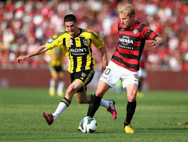 Aaron Mooy of the Wanderers competes for the ball against Corey Gameiro of the Phoenix during the round 24 A-League match between the Western Sydney Wanderers and the Wellington Phoenix at Parramatta Stadium on March 10, 2013 in Sydney, Australia.