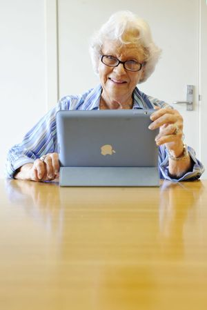 Vi Jorgensen looks at her new iPad. Senior Net has extended its training program to include course for seniors using tablet devices.