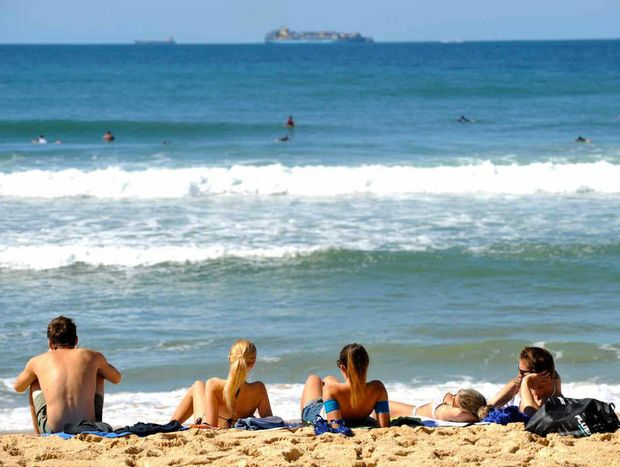 A beautiful clean break at Buddina under blue skies had sun-kissed beachgoers watching surfers and ships heading into the Port of Brisbane.
