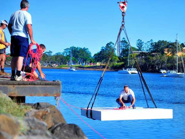 STILL AFLOAT: Scott Hudson is lowered on to the water as he works on the installation of the Bundaberg Rowing Club's pontoons at the city reach of the Burnett River. Photo: Ben Turnbull / NewsMail