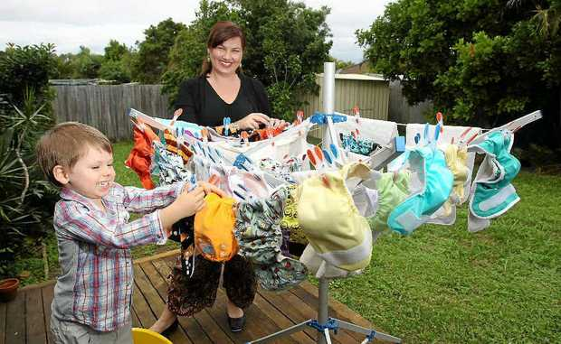 Archer Earl, 3, helps his mum Carly Earl hang cloth nappies on the clothesline. These reusable nappies save on landfill space.