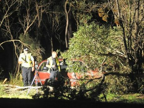 Police investigate one of the vehicles involved in the two-vehicle crash on Booral Rd.
