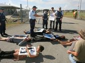 FOUR protesters who laid down on the road in front of military supply vehicles have been arrested in Rockhampton.