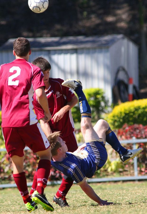 CQFC player Jordan Miller kicks the ball over his head in a shot at goal in the soccer game against QAS on Sunday. Photo: Chris Ison / The Morning Bulletin