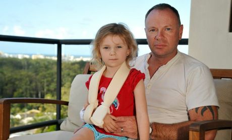 Chelsea Fletcher, 5, with dad Howard, of Buderim, was hit by a cyclist at Mooloolaba and suffered a broken collar bone, multiple abrasions, a cut head, cut knees, cut elbows, cut ankle, tyre marks on her back and bruising. Photo: Iain Curry / Sunshine Coast Daily