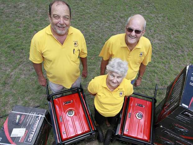 LIONS TO THE RESCUE: Bundaberg Lions President Rino Gastaldo, Robyn Pohlmann and Geoff McColl with the new generators. Photo: Simon Young / NewsMail