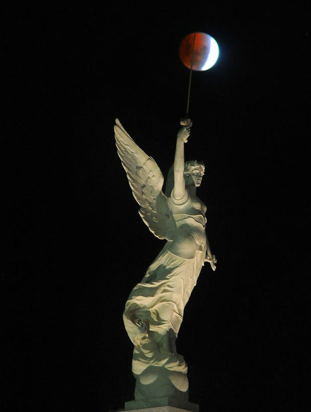 The blood moon of April 15 passes over the winged figure of victory gracing the cenotaph at Queens Park in Maryborough.