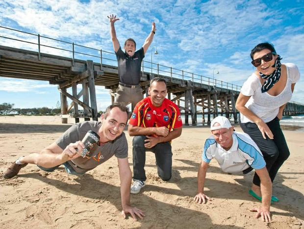 ON TRACK: Anthony Donovan (kneeling) joins supporters Luke Floyd, Rob Hoy, Michael Dougherty and Nicole Donovan in a workout on Jetty Beach. Rob Wright