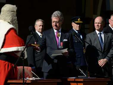 Former Queensland Chief Justice Paul de Jersey AC (centre), is given a bible by Chief Justice Tim Carmody (left) and joined by Premier Campbell Newman (right), as he is sworn in as Governor of Queensland at Parliament House in Brisbane, Tuesday, July 29, 2014. Mr de Jersey will become the 26th Governor of the state, replacing Ms Penelope Wensley.
