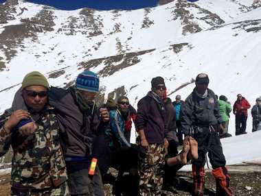 Nepal Army personnel helping survivors to an Army helicopter in the Manang district along the Annapurna Circuit Trek.