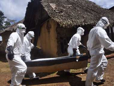 Health workers carry the body of a suspected Ebola victim in Bomi county on the outskirts of Monrovia, Liberia