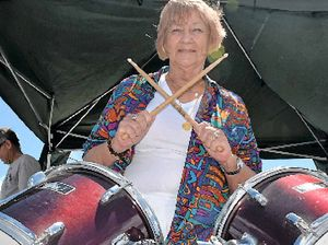 DRUMMING UP BARGAINS: Whitsunday Regional Councillor Jan Clifford behind a set of drums for sale at Saturday's Garage Sale Trail in Airlie Beach.
