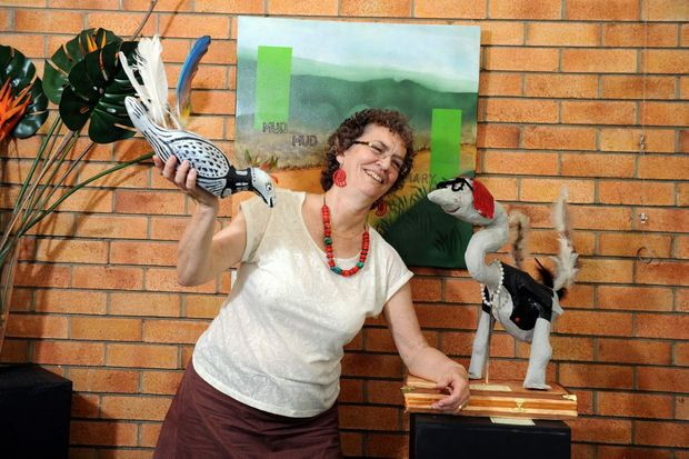 ann bowden poses with a couple of her sculptures featured