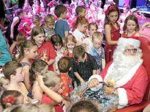 HO HO HO: Santa is mobbed by excited children at Carols by the Beach, held in the Whitsunday PCYC on Sunday evening.