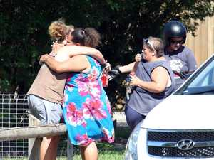 Distraught locals embrace at the scene after eight children were found stabbed to death at a house in Manoora near Cairns.